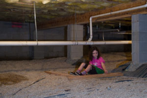 young girl sitting under home in crawlspace